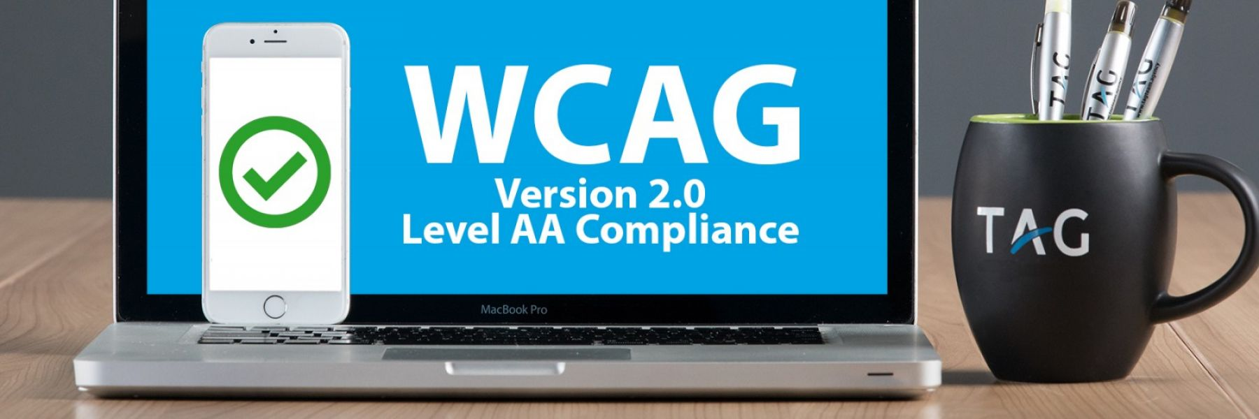 WCAG 2.0 AA compliance image in the TAG brand displayed on a desktop computer