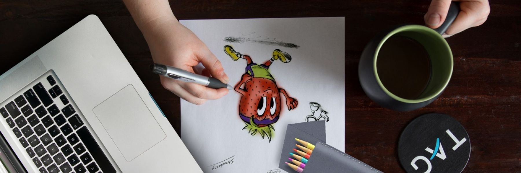 Person designing the QCHI animated strawberry on a wooden desk top on paper.