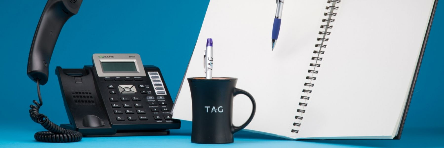 TAG PR Services. Picture of TAG phone, notebook and pens.